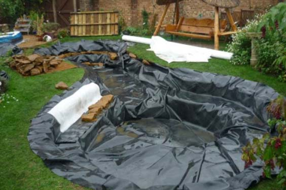 Pond liner spread out and secured using rocks